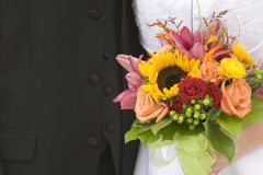 Bride and Groom Closeup with Bouquet. A bride and groom stand close together behind a colorful bouquet of flowers Stock Photography