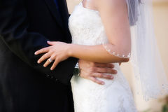 Bride and groom. Closeup of the midsections of a bride and groom facing each other Royalty Free Stock Photos