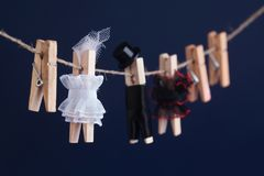 Bride and groom clothespin toys, clothesline. Abstract woman in white dress and man character with black suit hat. Love. Concept photo. Macro view, shallow Royalty Free Stock Photos