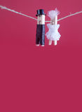 Bride and groom clothespin toys on clothesline. Abstract woman in white wedding dress and man with suit hat. Love. Concept photo. Macro view, shallow depth of Royalty Free Stock Photo