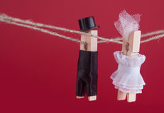 Bride and groom clothespin toys on clothesline. Abstract woman in white wedding dress and man with suit hat. Love. Concept photo. Macro view, shallow depth of Stock Photography