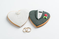 Bride and groom cookies and wedding bands Royalty Free Stock Photography