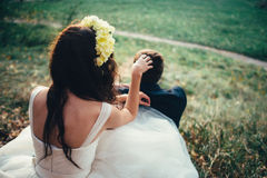 Bride and groom with corolla in a forest. Touching the head groom Stock Image