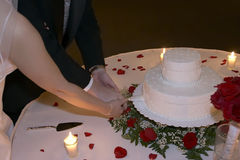 Bride and Groom Cut Wedding Cake by Candlelight. Happy newlyweds cut the cake at their reception over candlelight Royalty Free Stock Photos