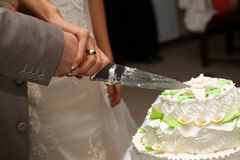 Bride and groom cut the wedding cake closeup Royalty Free Stock Photo