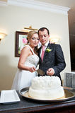 Bride and groom cuts wedding cake Royalty Free Stock Image