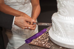 Bride and groom is cutting the cake during the wedding ceremony Stock Photo