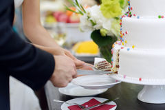 A bride and a groom cutting their wedding cake Stock Photos