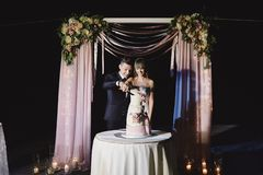 A bride and a groom is cutting their wedding cake. beautiful cake. nicel light. wedding concept.  royalty free stock photography