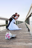 Bride and Groom dance. A bride and military groom dancing and kissing on a boardwalk outdoors stock photos