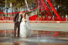 Bride and a groom dance near the fountain Royalty Free Stock Images