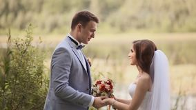 The bride and groom dance outdoors in a park near the lake. Happy together. Wedding day. stock video