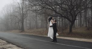 Bride and groom, dance and play with emotion on the road near forest,slow. 4k stock video