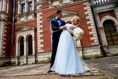 The bride and groom dancing around the columns of the old estate. A tall groom, and a bride with blond hair. Blue stock image