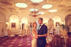 Bride and groom dancing in empty restaurant Stock Photos