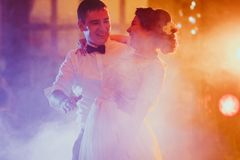 Bride and groom dancing the first dance in the blurry background.  Royalty Free Stock Photography