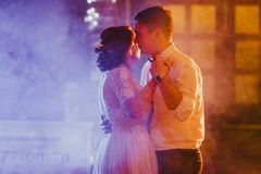 Bride and groom dancing the first dance in the blurry background.  Royalty Free Stock Images