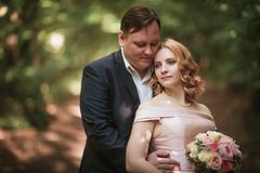 Bride and groom dancing in the forest background and sunlight royalty free stock photography