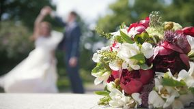 Bride and groom dancing in front of wedding bouquet, slow-motion