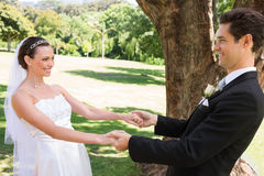 Bride and groom dancing in garden. Happy bride and groom holding hands while dancing in garden Stock Photos