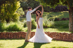 Bride and groom dancing in garden wedding. Bride and groom dancing outside garden wedding ceremony Stock Image