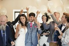Bride And Groom Dancing With Guests. Bride and groom are dancing and raising their glasses with the guests on their wedding day Royalty Free Stock Image