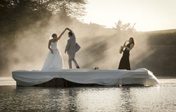 Bride and Groom dancing on a lake to music. royalty free stock photography