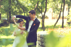 Bride and groom dancing in the park Stock Photos