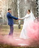 Bride and groom dancing at park at red smoke Stock Image