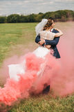 Bride and groom dancing in red smoke at sunny day Stock Images