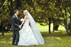 Bride and groom dancing together outside on their wedding day - Stock Images