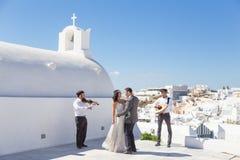 Bride and groom dansing on wedding ceremony on Santorini island, Greece. Stock Photo