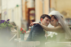Bride and groom daydream somewhere in the street-cafe. A Royalty Free Stock Image