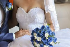Bride and groom details. Bride and together with blue flower bouquet Stock Photos