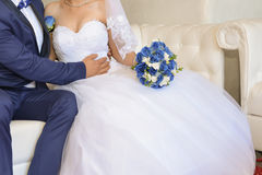 Bride and groom details. Bride and groom together holding flower bouquet Royalty Free Stock Photo
