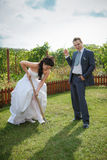 Bride and groom digs the soil on a kitchen garden. Stock Image