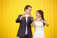 Bride and groom doing love sign Royalty Free Stock Photo