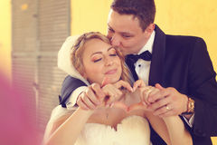 Bride and groom doing love sign with their hands Stock Photo