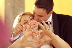 Bride and groom doing love sign with their hands Royalty Free Stock Photography