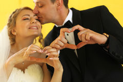 Bride and groom doing love sign with their hands Royalty Free Stock Image