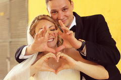 Bride and groom doing love sign with their hands Stock Photography