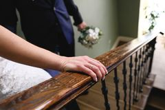 The bride and groom down the stairs, the bride`s hand close-up. Wedding day royalty free stock photography