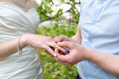 Bride groom dresses a wedding ring on her finger.  royalty free stock photography