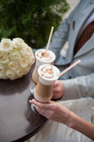 Bride and groom drink latte with painted hearts Royalty Free Stock Photography