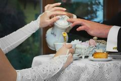 The bride and groom drink tea at the cafe. stock photo