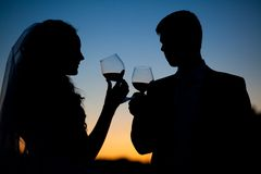 Bride and groom drink wine at sunset Stock Photo