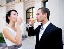 Bride and groom drinking champagne outdoors Royalty Free Stock Photography