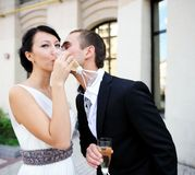Bride and groom drinking champagne outdoors Stock Photos