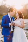 Bride and groom drinking red wine holding glass touching each other. Shiny sun at background Stock Image
