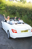 Bride And Groom Driving Away In Decorated Car Royalty Free Stock Image